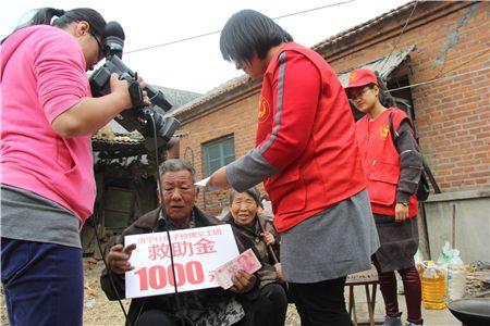 看到玫瑰义工团为老两口拿来的大米和食用油,朱龙华老人感动不已.